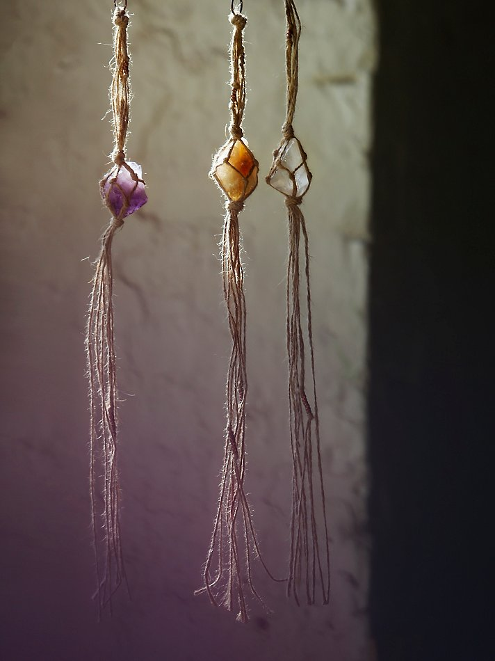 Image: three small crystals hanging in raffia macrame.